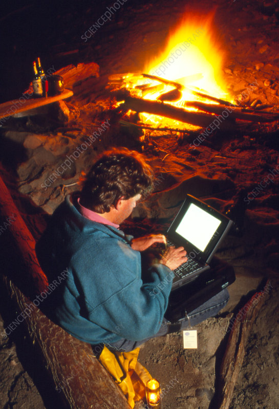 Man using a laptop computer by a campfire