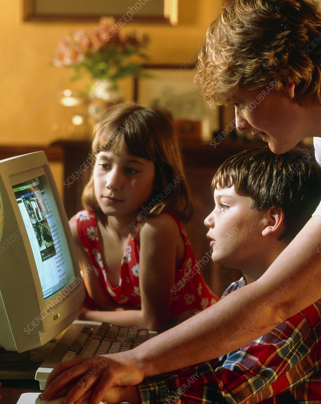 Mother helping her children to use a home computer