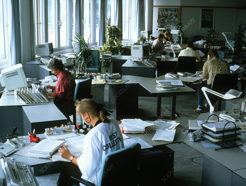 Workers using computers in an open plan office