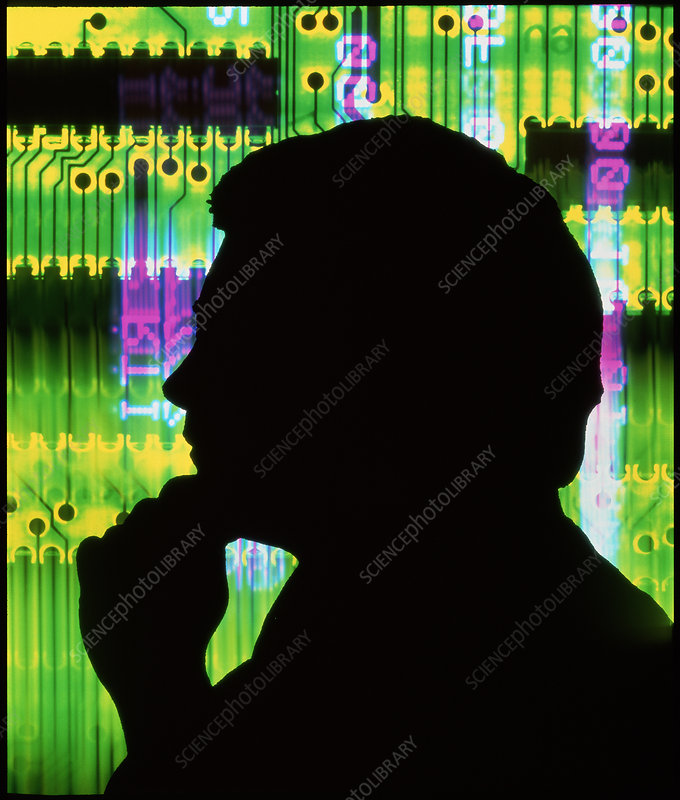 Silhouette of man against circuit board
