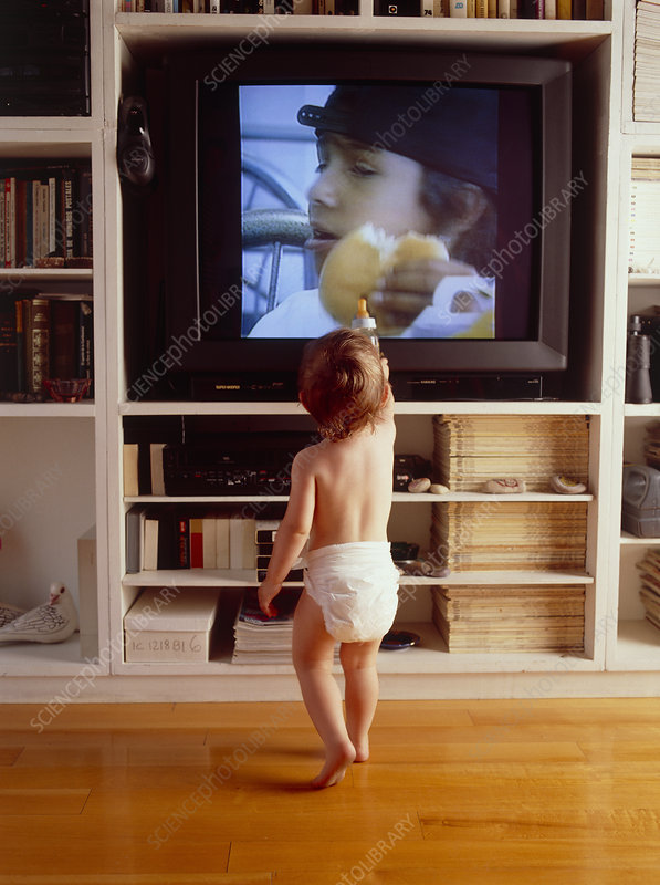 Young child stands and watches television