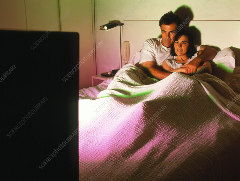 Man and woman watch television in bed