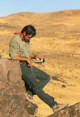 Field geologist using hand-held GPS receiver