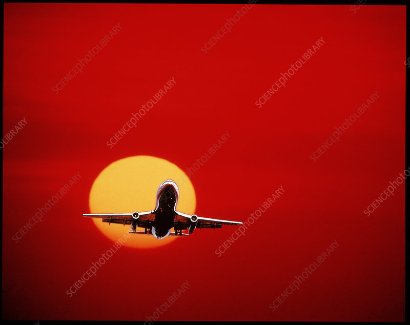 Airliner landing against a setting Sun