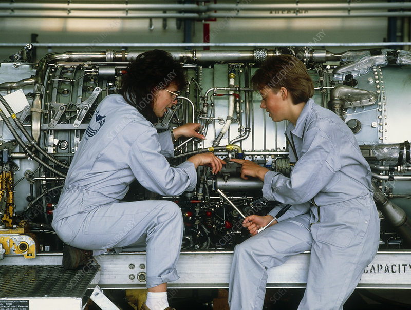 Female engineers assembling an aircraft jet engine