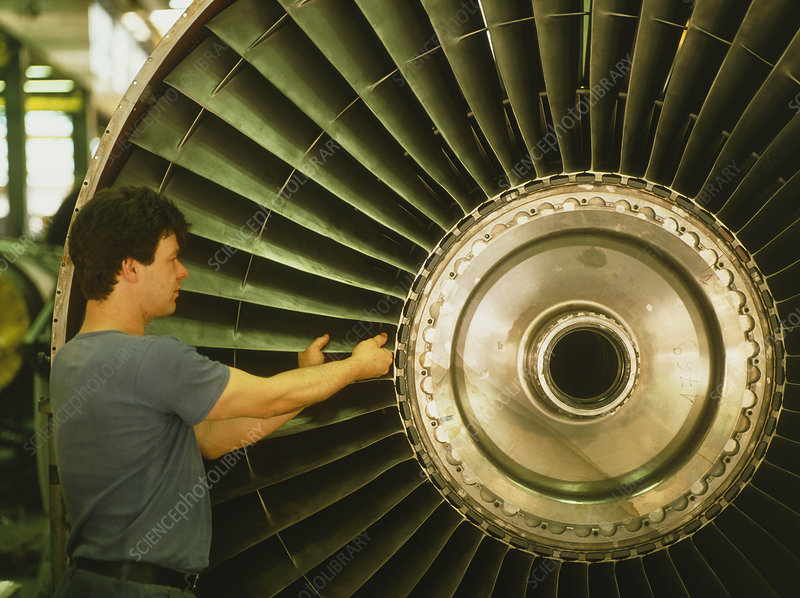 Technician assembles part of a jet engine