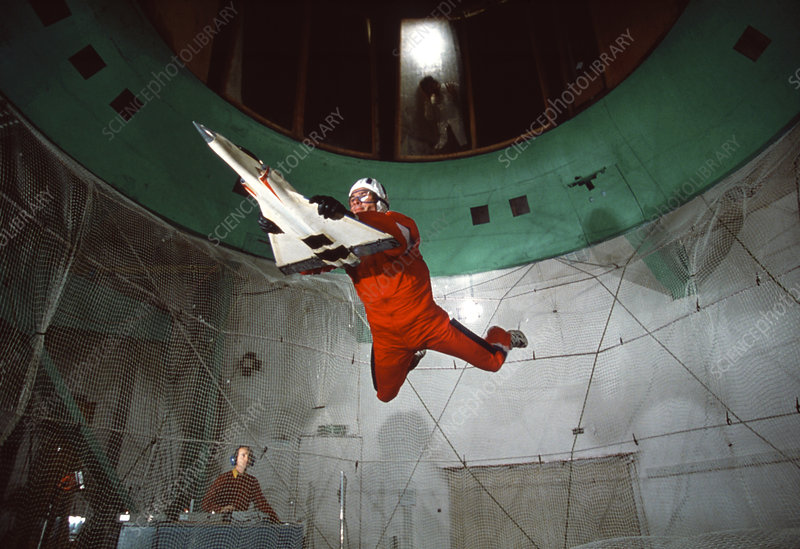 Man with aircraft model in a vertical wind tunnel