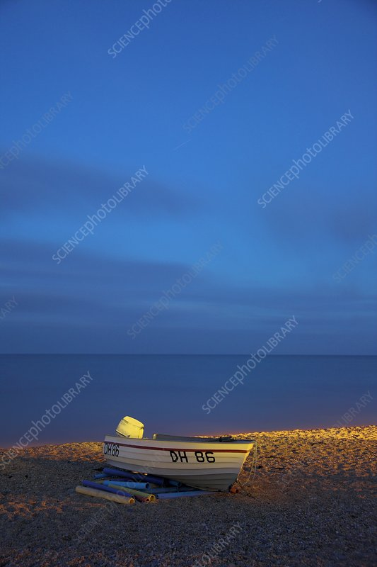 Boat moored on a beach at dusk