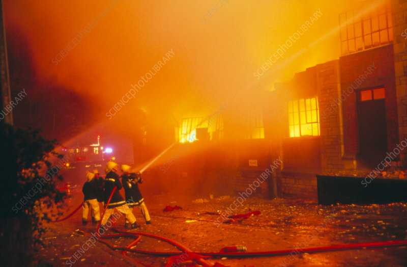 Fire fighters hosing a fire at a piano factory