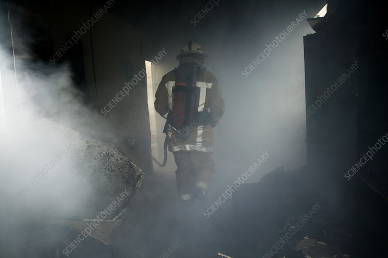 Fire fighter in a burnt house