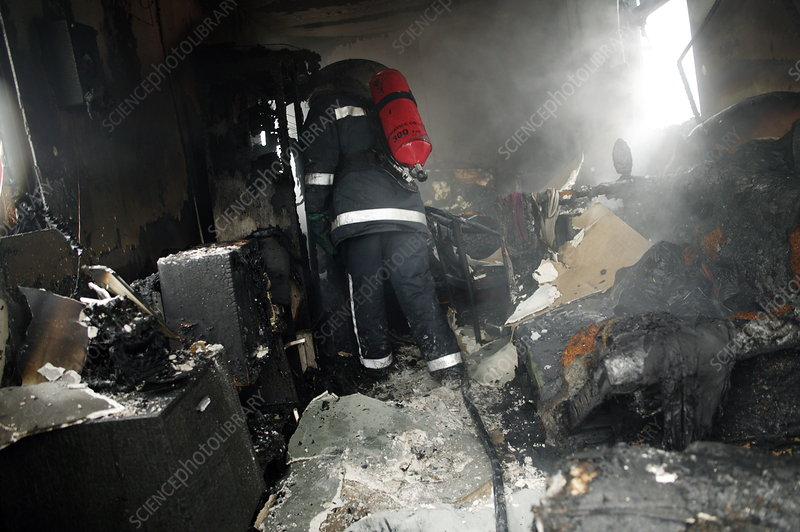 Firefighter in a burnt-out house