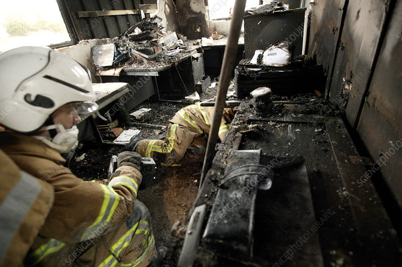 Firefighters in a burnt-out house