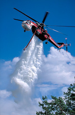 Helicopter drops water over forest fire