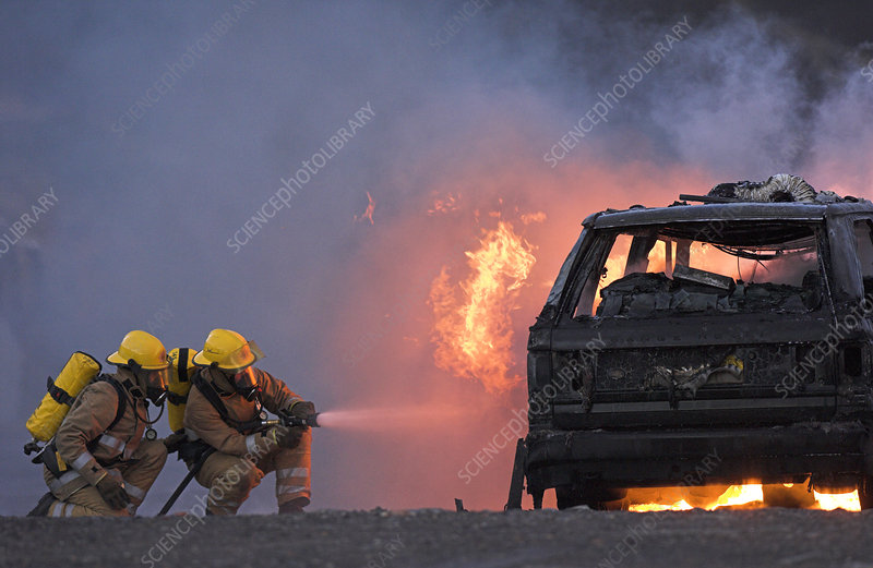 Firefighters hosing a burning car