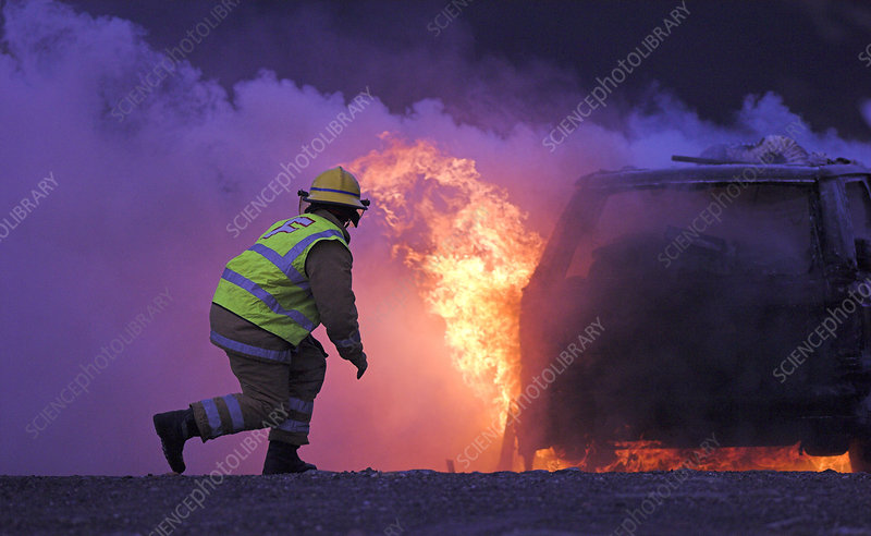 Firefighter tackling a burning car