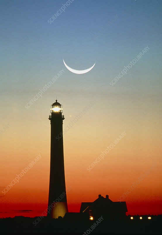 Crescent moon over lighthouse at sunrise