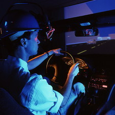 Man uses a car driving simulator