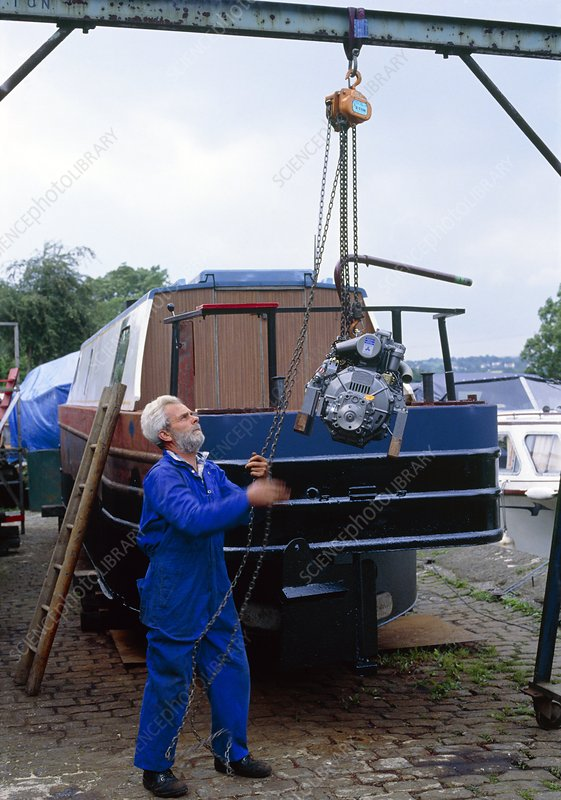 Engineer using block & tackle to lift boat engine