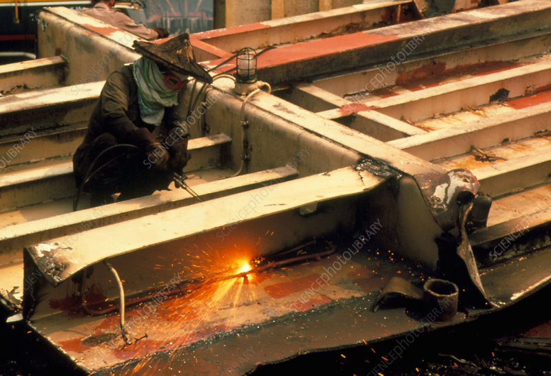 Worker using gas cutting torch in shipyard