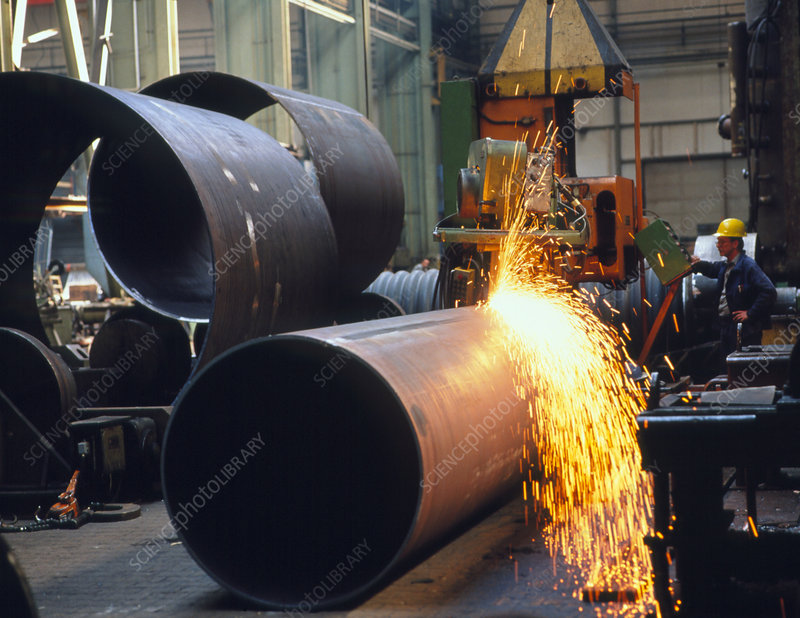Man welding a boiler pipe with a welding machine.