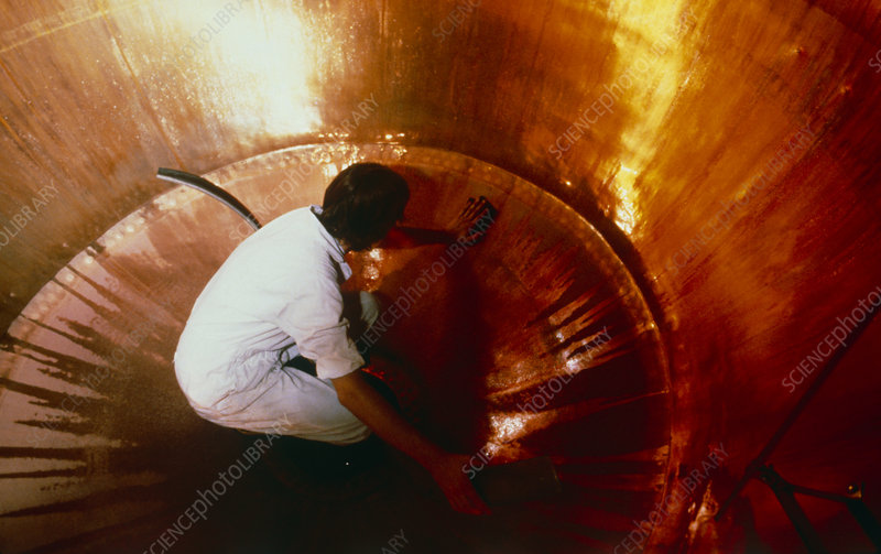 Man cleaning inside of brewery vat