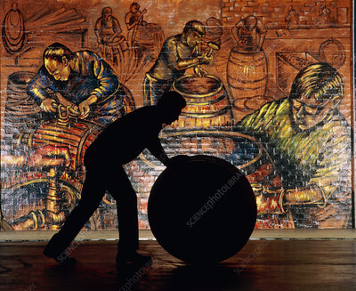 Silhouette of whisky worker rolling whisky cask