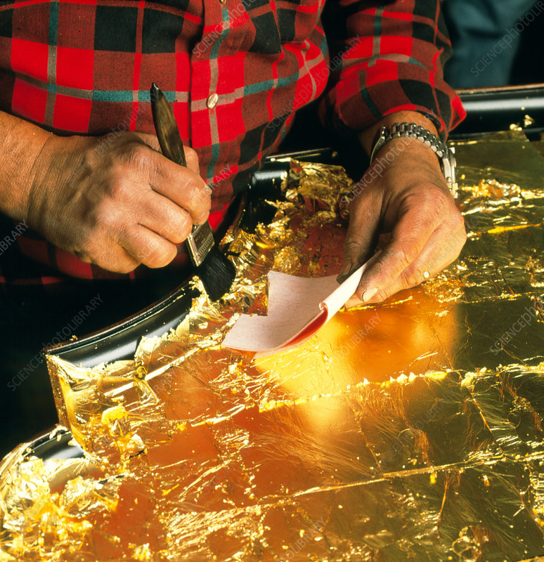 Craftsman applies gold leaf to a table top