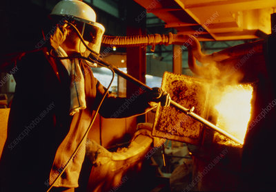 Steel worker checking contents of furnace