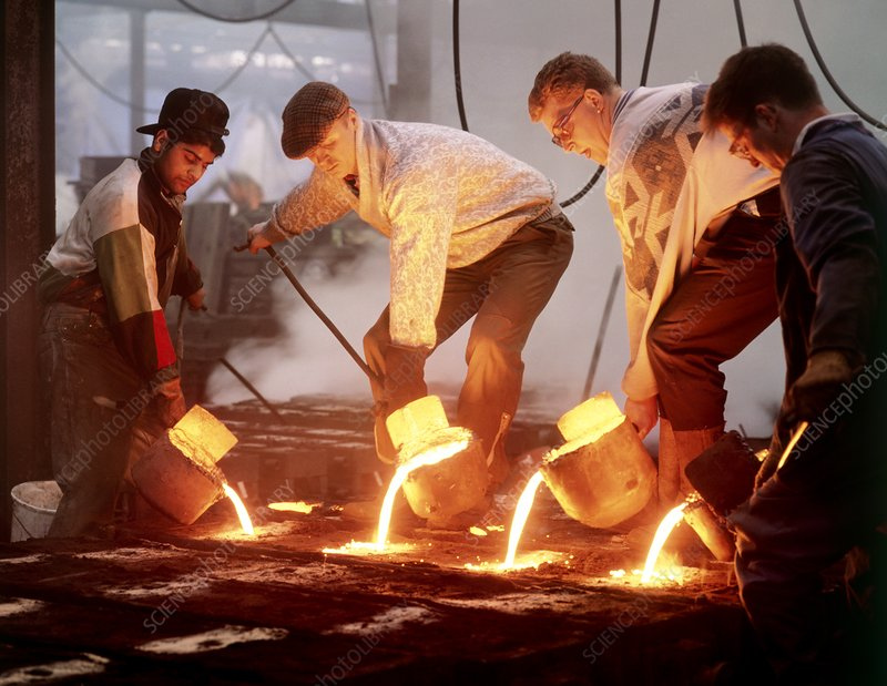 Foundry workers pouring hot metal into moulds