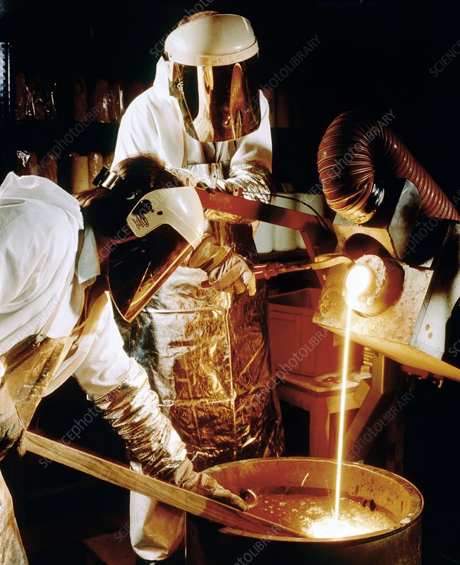 Foundry workers pouring molten metal into an ingot