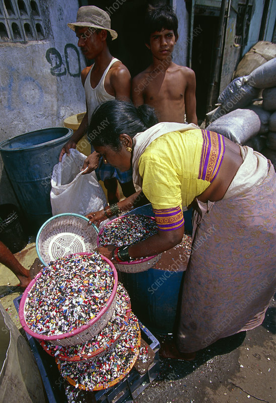Woman sorting plastic waste to separate out PVC