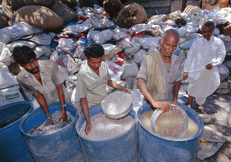 Men sorting plastic waste to separate out PVC