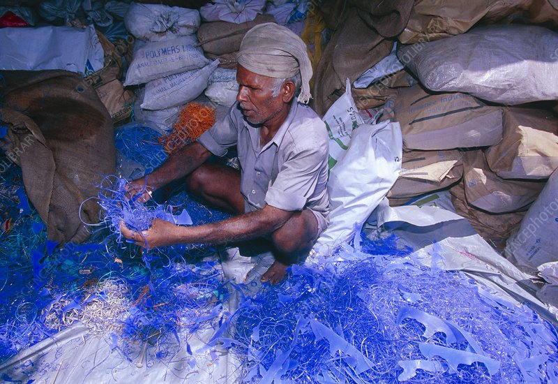 Man sorting plastic waste to separate out PVC