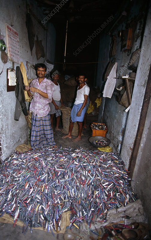 Workers with a pile of plastic pens for recycling