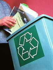 Person placing paper in a recycling bin