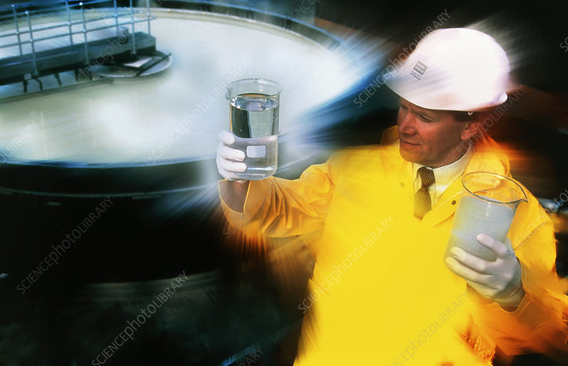 Worker holds treated and untreated water samples