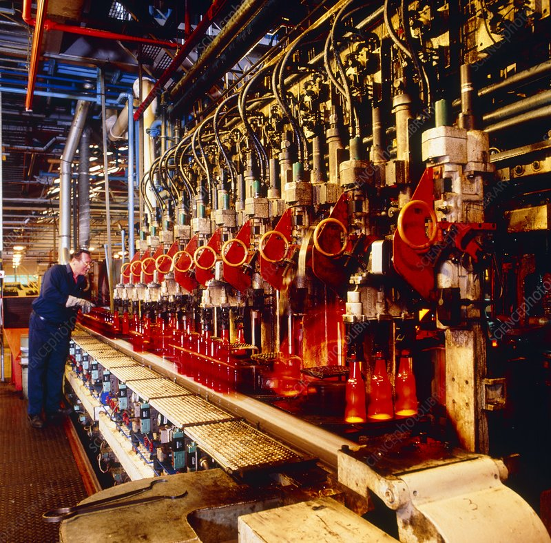 Technician checks production line of glass bottles