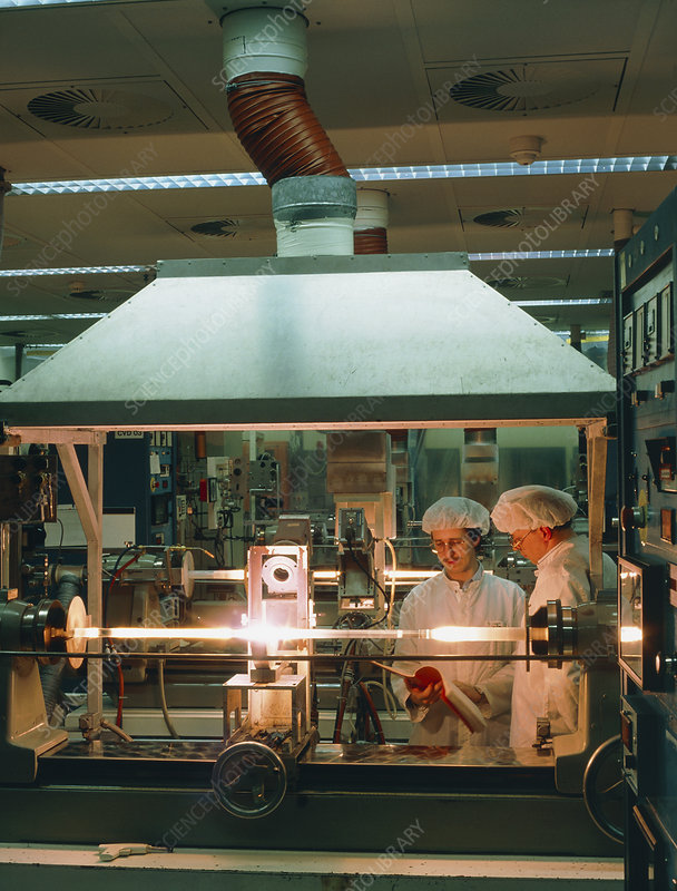 Workers making a glass blank for an optical fibre