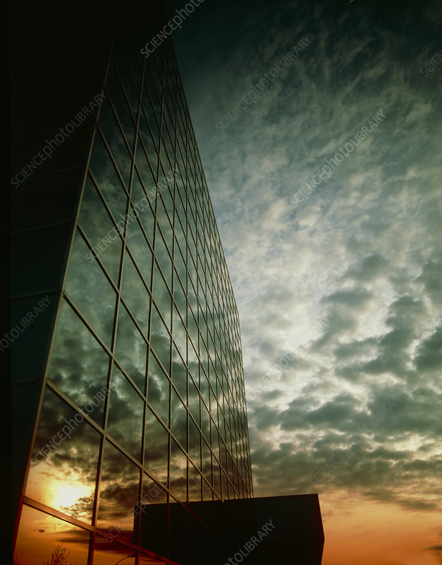 Glass building reflecting clouds