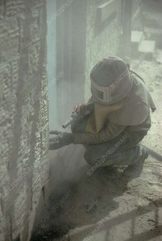 Man in protective clothing using sand blaster