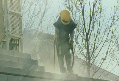 Man in protective clothing sand blasts a building