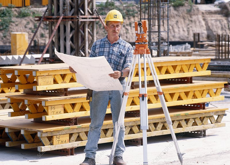 Foreman surveying a building site with a theodolit