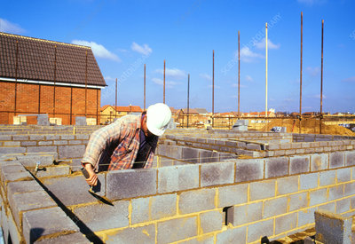 Bricklayer constructing a wall from breeze-blocks