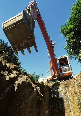 Mechanical digger excavates ditch on building site