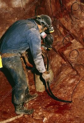 Worker laying explosives in uranium mine