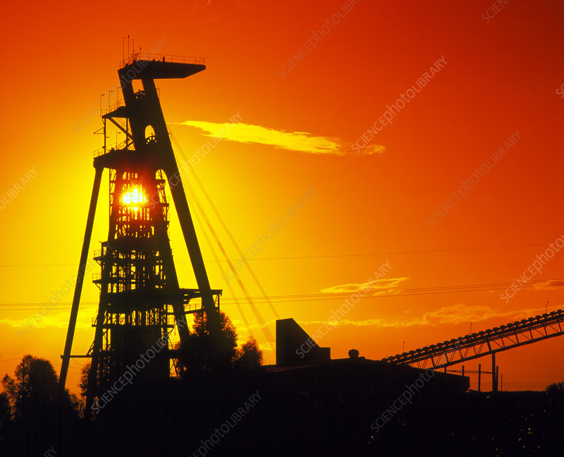 Head frame over shaft of gold mine at sunset