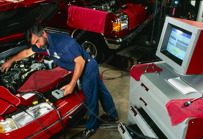 A mechanic testing a car engine with a computer