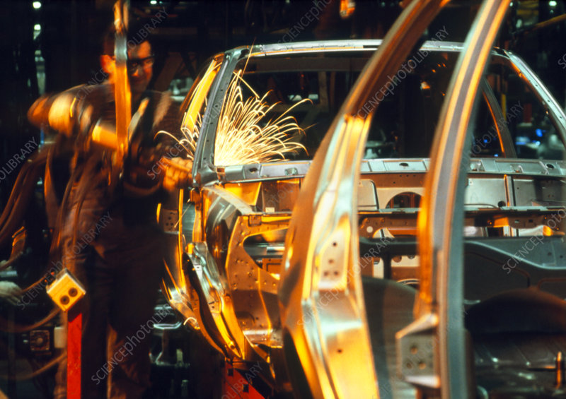Technician welding in a car body production line