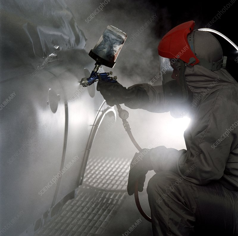 Caption: Spray painting a car. Worker dressed in protective clothing