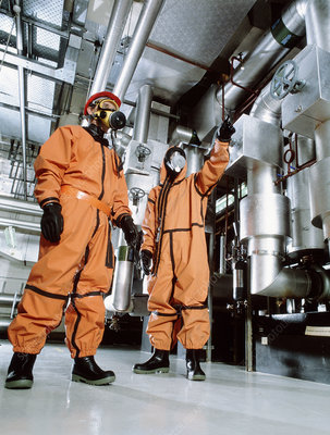 Workers in a factory wearing chemical suits